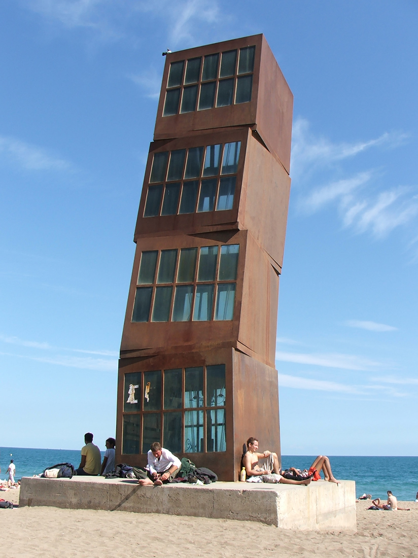 people sitting below a sculpture of large metal blocks forming a crooked tower on a beach