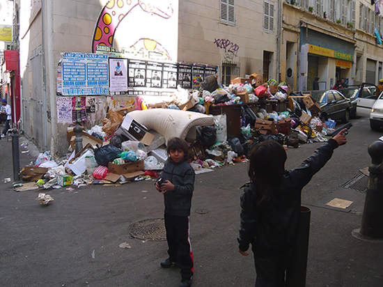 children playing with toy guns with piles of rubbish in the background