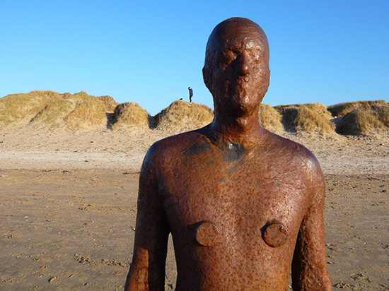 cast-iron, life-size figure against blue sky with sand dunes in the background.