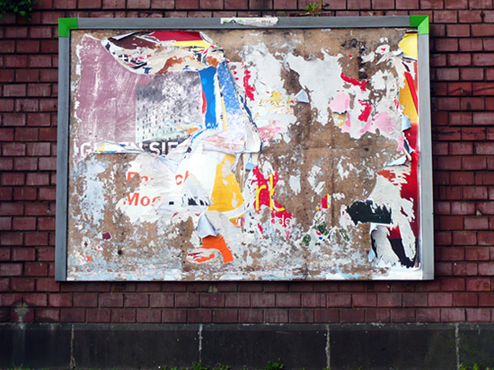 empty advertising billboard on a brick wall, showing fragments of old posters
