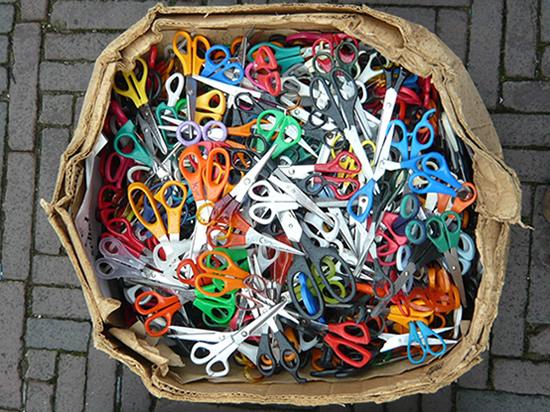 cardboard box full of scissors with brightly coloured handles