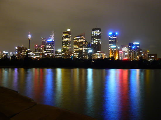city skyline at night reflected in water