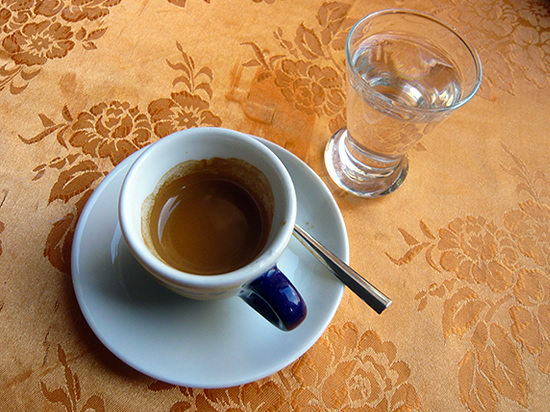 a cup of espresso coffee and a small glass of clear grappa liqueur on a velveteen, floral table cloth
