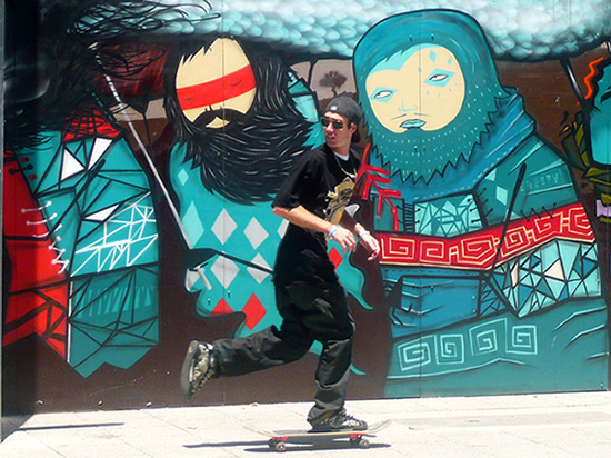 man skateboards in front of graffiti Inuit