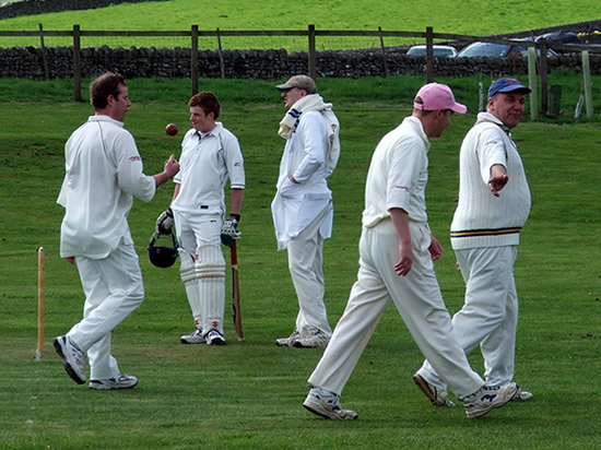 a group of men dressed in cricket whites walking across a cricket pitch