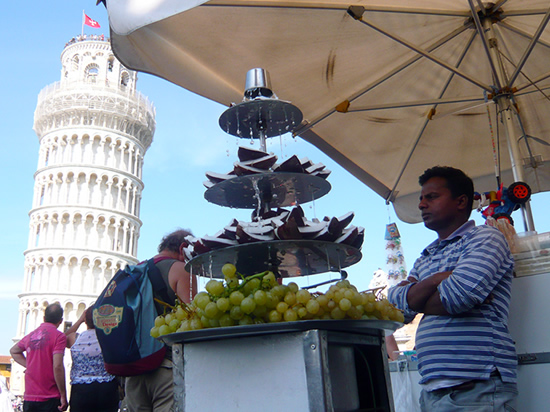 stall selling coconut and grapes in front of the leaning tower of Pisa