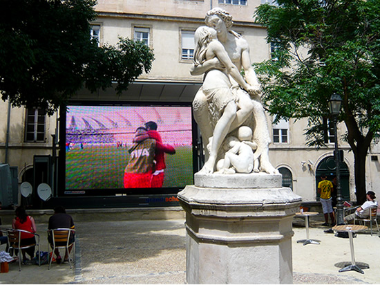 statue of lover embracing, a arge screen in the background shows an image of two footballers embracing to celbrate a goal