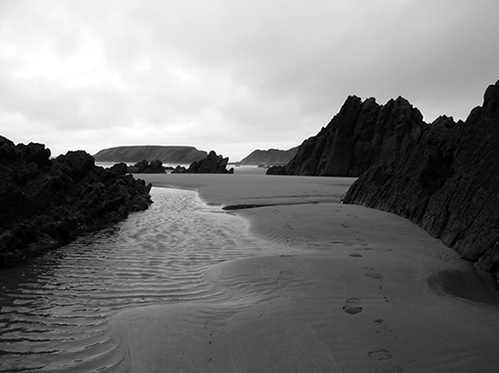 Black and white photo rock formations and poosl on a beach.