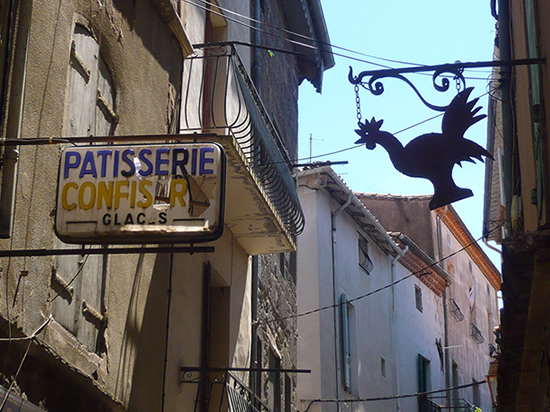 """a damaged plastic sign in french """"Pâtissier Confiseur Glaces"""". a second sign of cockerel cockerel silhouette"""