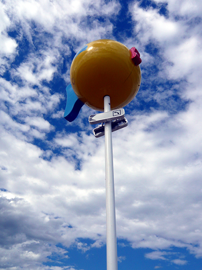large plastic fish against a blue sky with white clouds