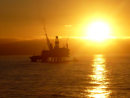 an oil rig siluetted against a bright sunrise