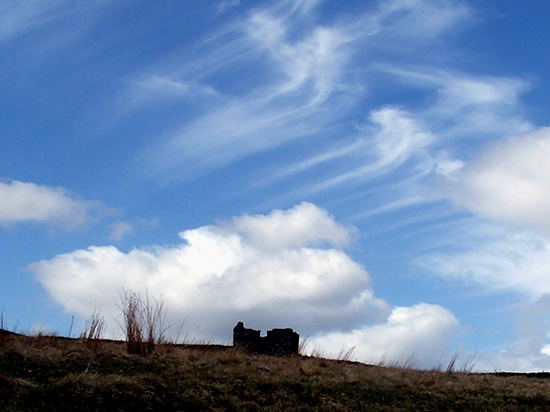 ruined house against a large cloud filled sky