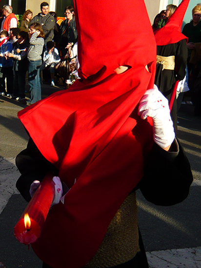 man wearing a red pointed hood with eye hoes and white gloves spattered with wax from a red candle