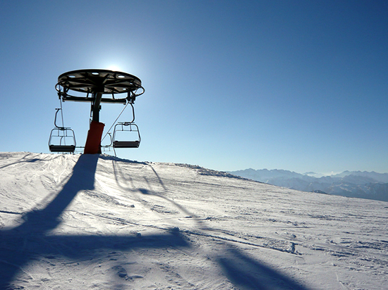 chairlift silhouetted against a blue sky, throwing a long shodow on the snow (telesillas y sombra)