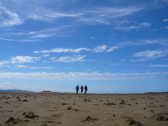 three figures walking on sandy beach to the horizon. sand against blue sky