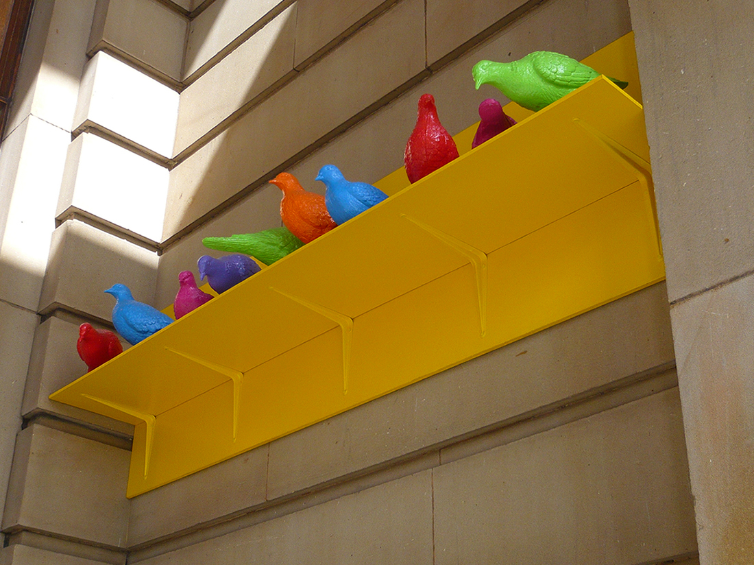 sculpture of brightly coloured pigeons on a bright yellow, metal shelf against a sandstone block wall