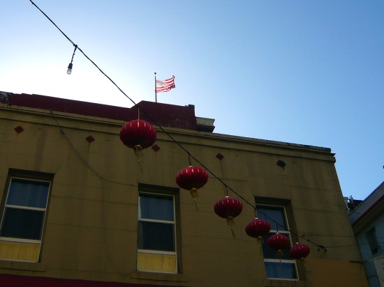 chinese lanters hanging in san francisco's china town, american flag (stars and stripes) flying against a blue sky in the background