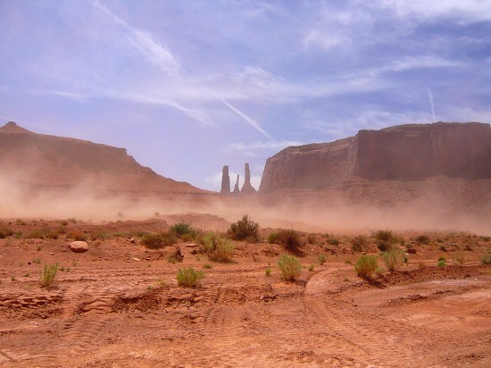 dust storm aproaching across the desert scrub land, tall cliffs and and three rock spires in the distance of monument valley