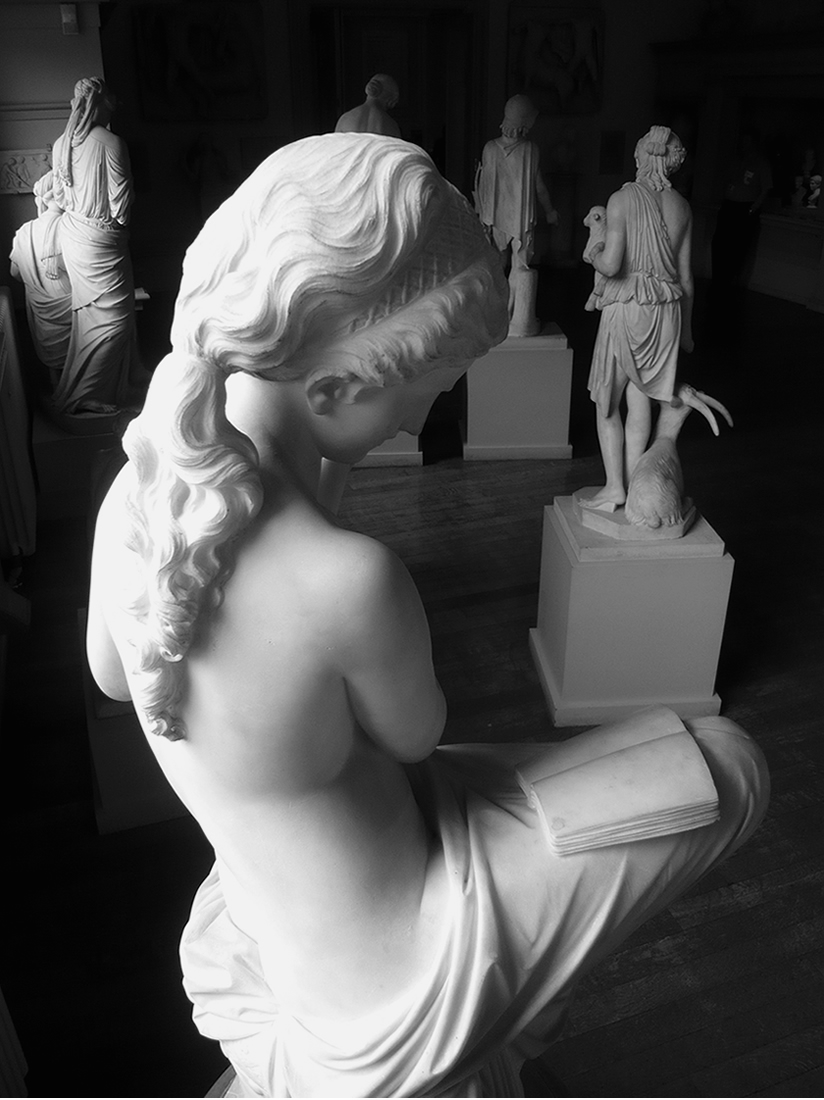 black and white photo of marble sculptures on plinths. in the fore ground a female figure reading