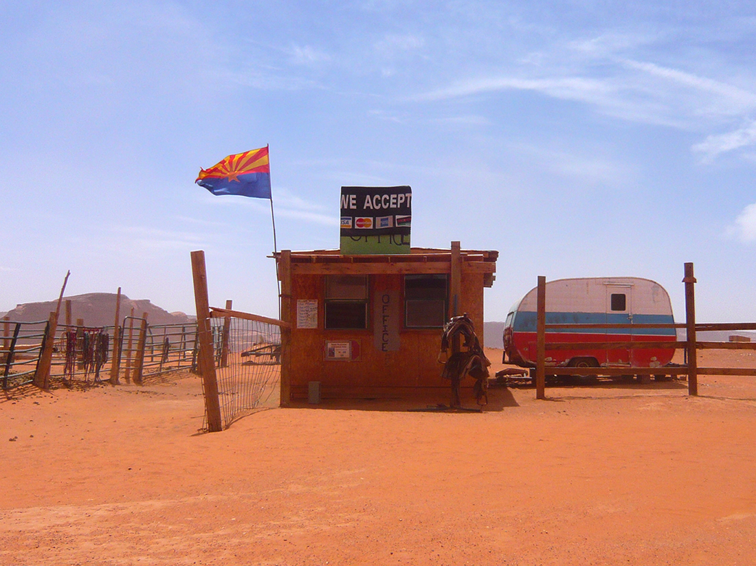 wodden shack in arrid landscape against blue sky,  displaying large  sign 'we accept'. a small carravan in to the right of the shack and the flag of arizona is flying on the shack roof.'