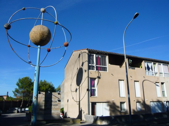 "large sculpture of an ""orrery"" or planetary model (representing spheres in orbit) casting a shadow on the side of a house"