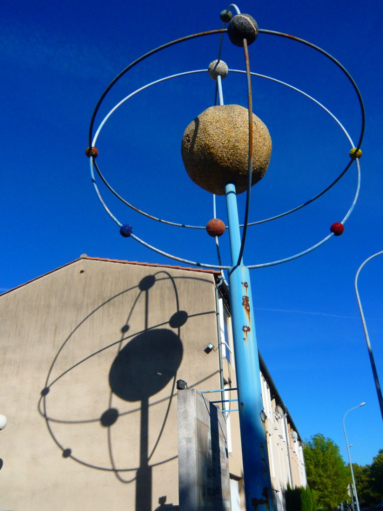 "rusting sculpture of an ""orrery"" or planetary model (representing spheres in orbit) casting a shadow on the side of a house"