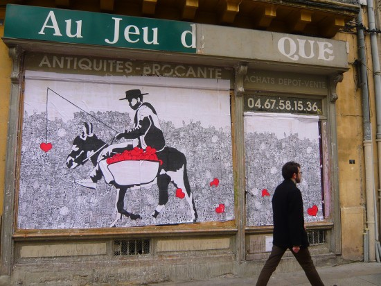 Man walks past a fly poster covering a shop window. The black and white illustration depicts a cow boy riding a donkey loaded with panniers, overflowing with red love hearts.