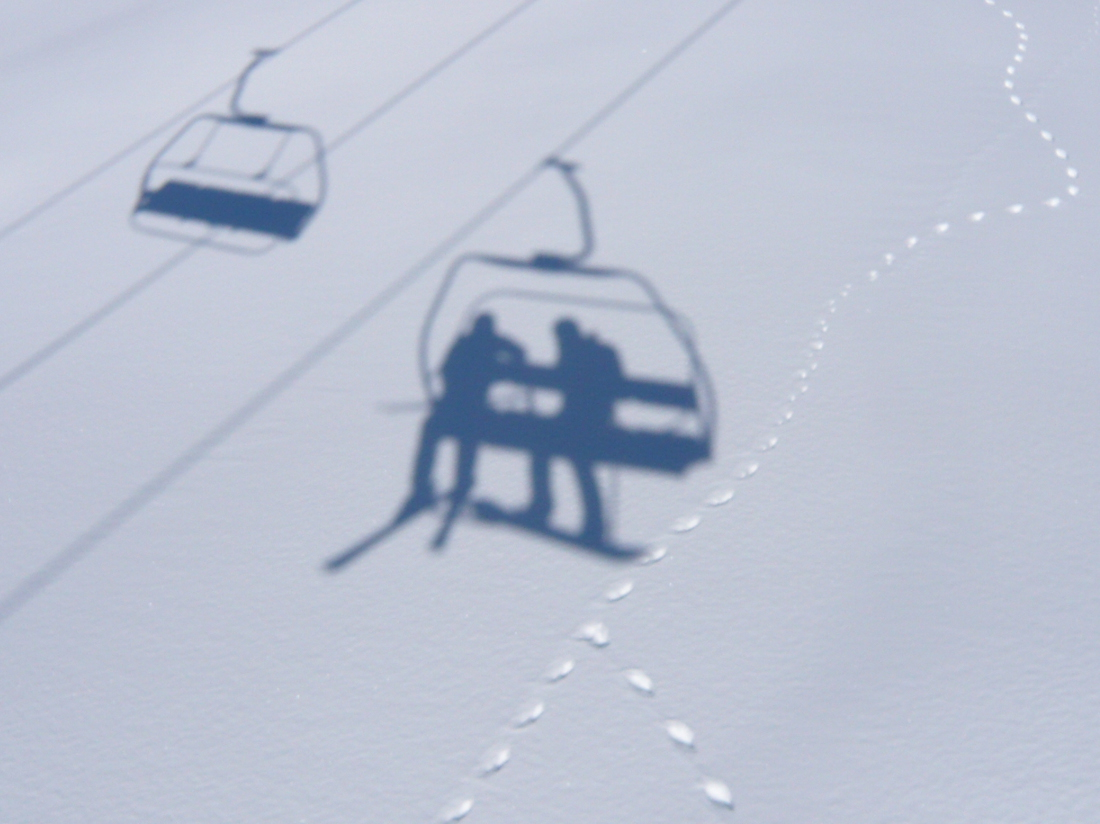 shadows of chairlift cast on snow and tracks of mountain hare on the snow surface