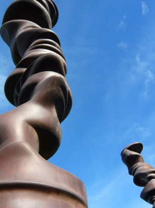 View of a bronze sculpture, consisting of abstract anthropomorphous forms piled on top of one another to form columns against a blue sky.
