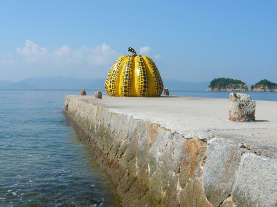 view of a large fiberglass, yellow pumpkin covered in with back dots on a stone pier surrounded by sea water with rocky islands in the distance