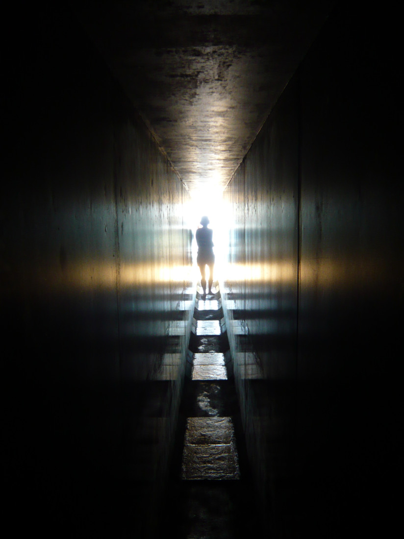 woman's silhouette against bright sunlight as she exists concrete lined passage