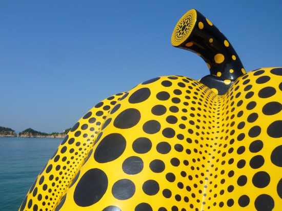 sculputure of large yellow pumking with back dots against a blue sky