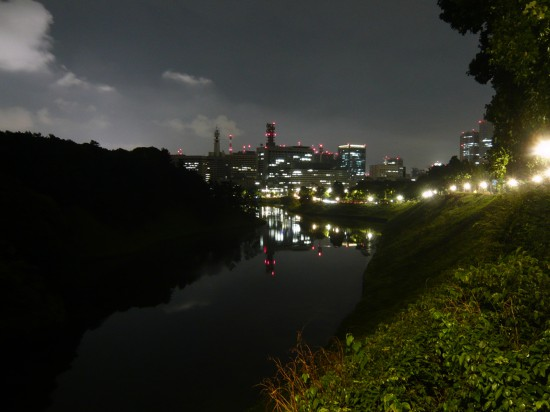 night scene of modern buildings and steet lights refelcted in a moat around a park