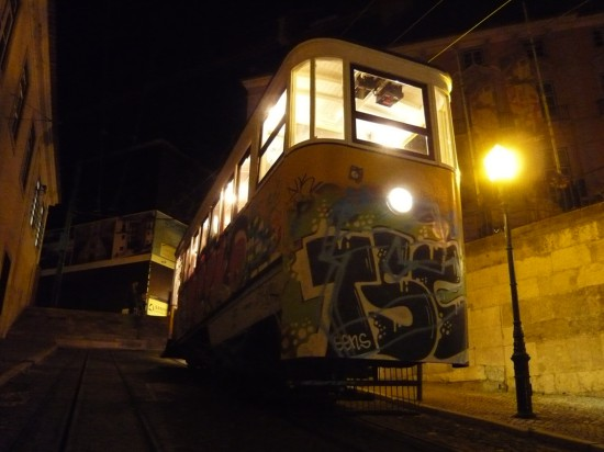tram on a steep hill at night illuminated by steet lamp and light from windows