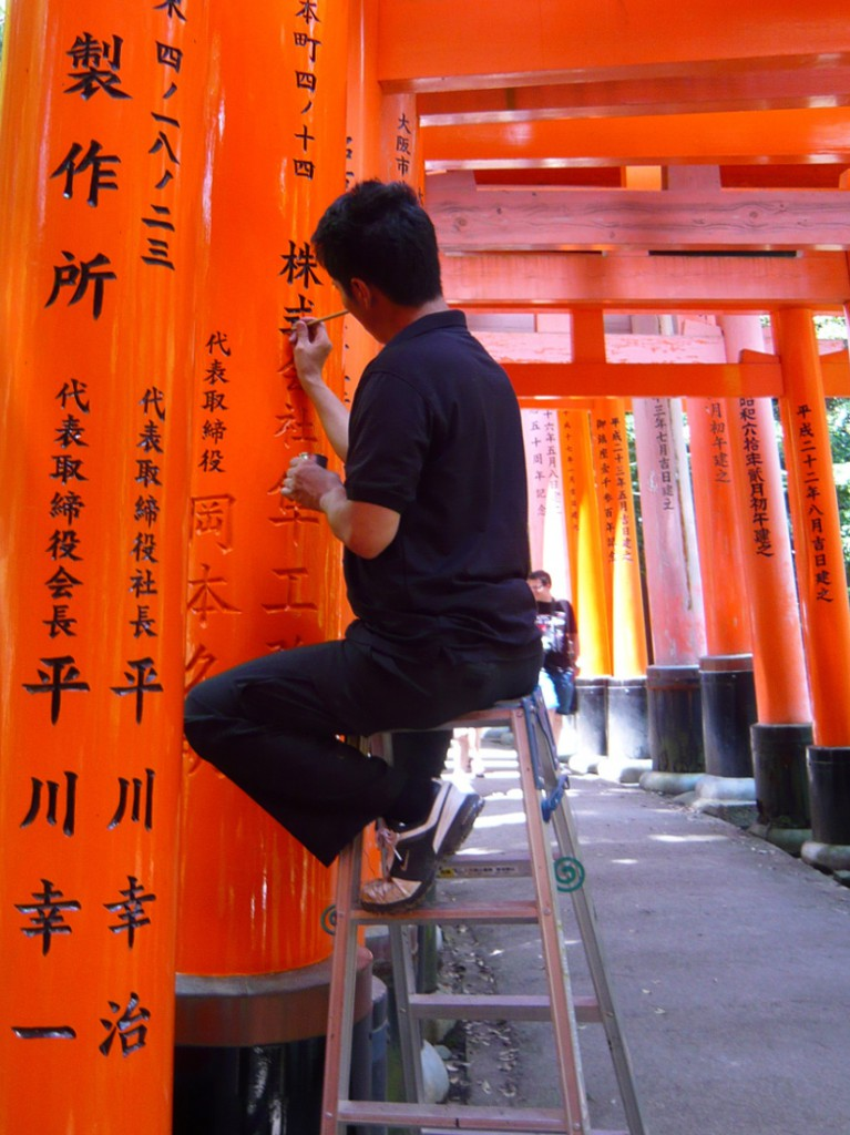man painting black Japaneese characters on a red vermillion arh