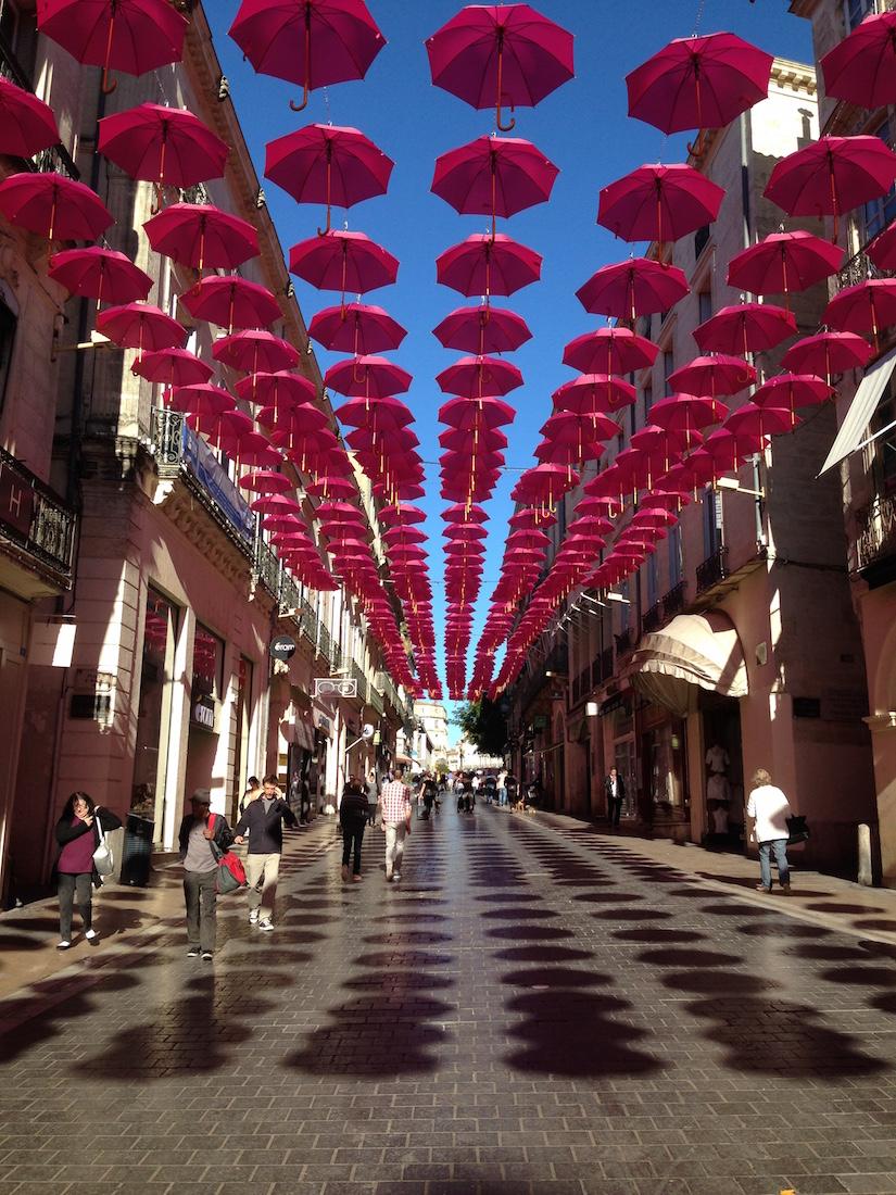 Pink umbrellas suspended above street