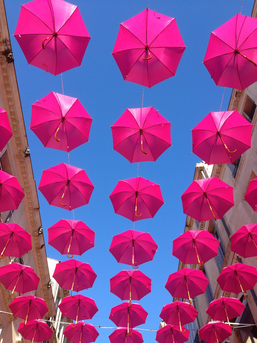 Rows of pink umbrellas suspended in the air against a blue sky